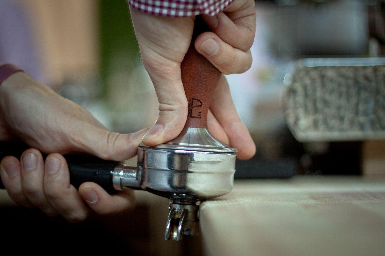 Свежесмолотый кофе в портафильтре, готовый для того, чтобы стать эспрессо