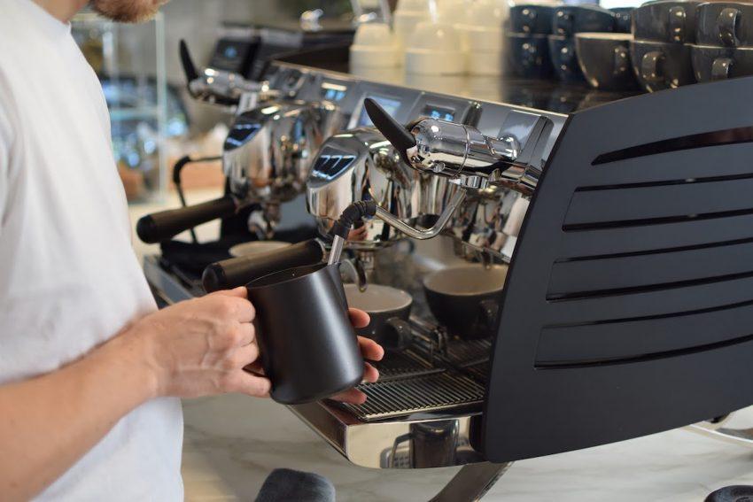 Бариста взбивает молоко в кофейне в Барселоне, Испания