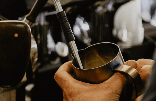 Бариста взбивает молоко