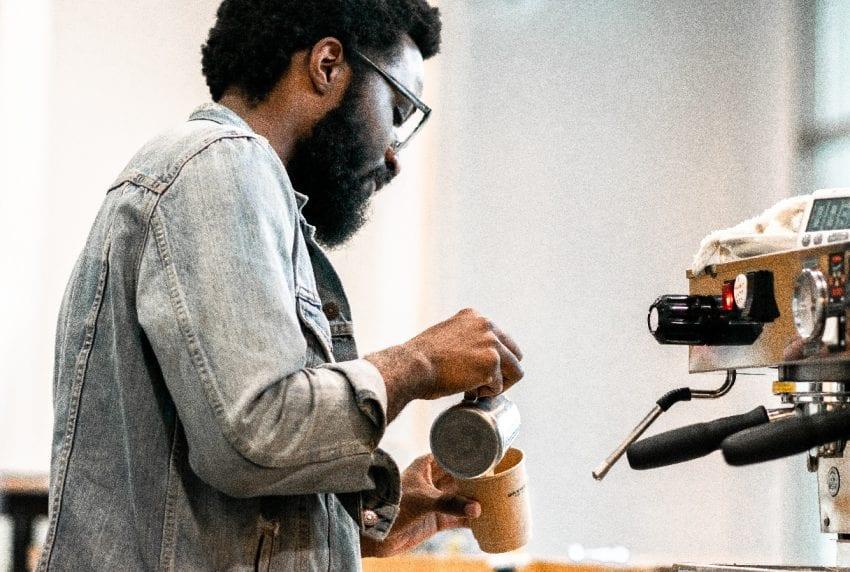 Бариста готовит кофе а бумажный стаканчик